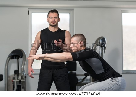 Personal Trainer Showing Young Man How To Train On Bosu Balance Ball In A Gym - stock photo