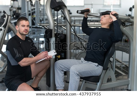 Personal Trainer Showing Young Man How To Train Shoulders On Machine In The Gym - stock photo