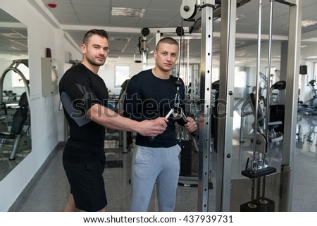 Personal Trainer Showing Young Man How To Train Triceps On Machine In The Gym - stock photo