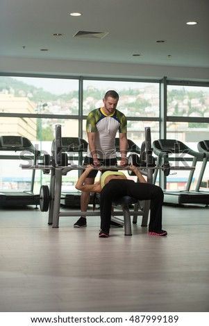 Personal Trainer Showing Young Woman How To Train Chest On Bench In The Gym