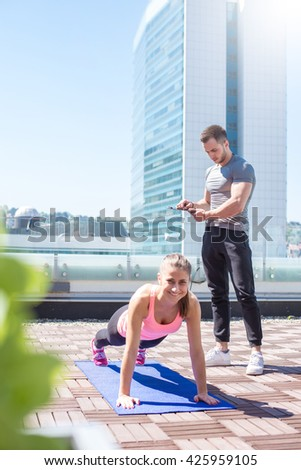 Personal trainer support and motivate his client while doing push ups outdoor. - stock photo