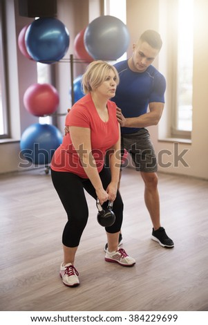 Personal trainer supporting mature woman - stock photo