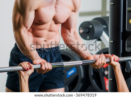 Personal trainer with barbell flexing muscles in gym - stock photo