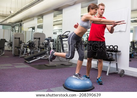 Personal trainer with client on bosu ball at the gym - stock photo
