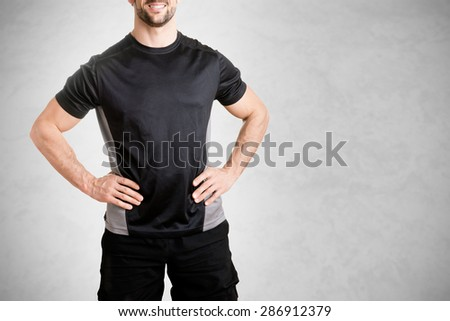 Personal trainer with is arms on his waist, isolated in grey - stock photo