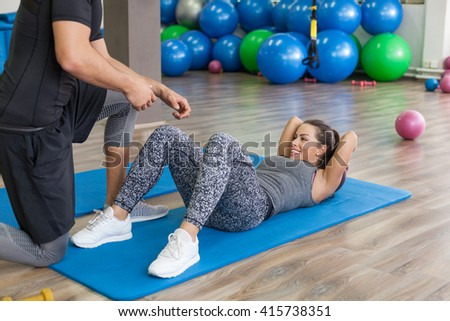 Personal trainer working with his client in gym - stock photo