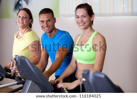 Personal trainer working with his clients. On treadmill, cardio workout. - stock photo
