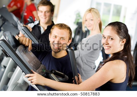 Personal trainers in the gym giving instruction and help to attractive young women - stock photo