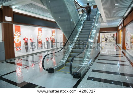 Persons on escalator in shop - stock photo