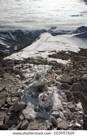 Persons traveling across arctic tundra in Svalbard archipelago - stock photo