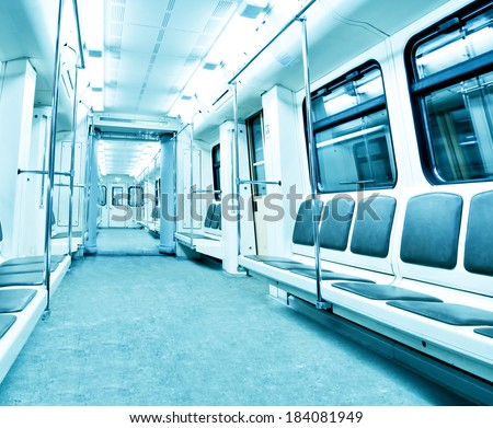 Perspective and diminishing wide angle view to Contemporary blue spacious interior and comfortable seats of modern train empty light illuminated wagon moving fast inside urban vanishing metro tunnel - stock photo