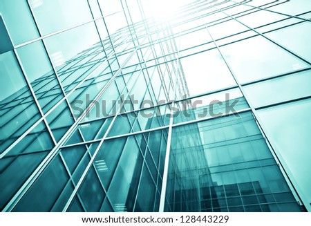 Perspective and underside angle abstract view to textured background of modern glass office building skyscrapers over blue cloudy sky at night
