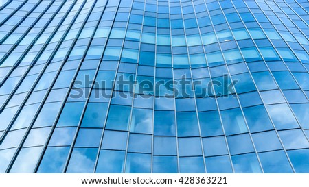 Perspective and underside angle view to textured background of contemporary glass facade of achitecture building skyscrapers with light reflect of sky and cloud. (Detail curve shape of glass mullion)