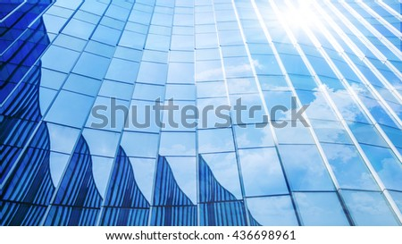 Perspective and underside angle view to textured background of contemporary glass facade of architecture building skyscrapers with the light reflect of sky and cloud. - stock photo