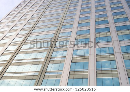 Perspective and underside angle view to textured background of mirror window glass building skyscrapers reflection with blue sky and white cloudy - stock photo
