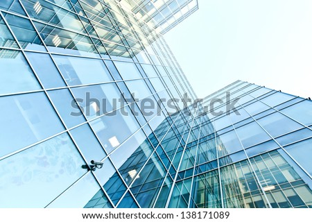 Perspective and underside angle view to textured background of modern glass building skyscrapers with mirrored reverberation over blue cloudless sky - stock photo