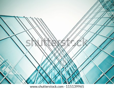 Perspective and underside angle view to textured background of modern glass building skyscrapers at night - stock photo