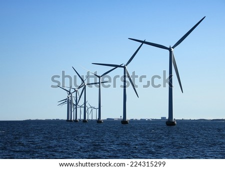 Perspective line of ocean windmills with dark water in back light - stock photo