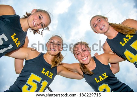 Perspective looking up with team of girls lacrosse players huddled close together, arms on each others shoulders, smiling and looking down at the viewer. - stock photo