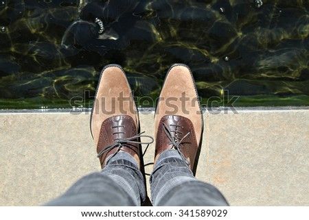 Perspective of a pair of smart shoes being worn by a man looking down. - stock photo