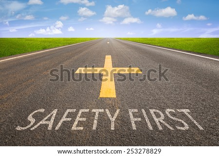 Perspective of asphalt road with safety first text. - stock photo