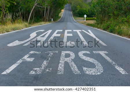 Perspective of asphalt road with safety first text, message on the road. Concept of safe driving and preventing traffic accident. - stock photo