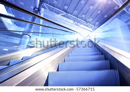 Perspective of escalator toned in blue color - stock photo