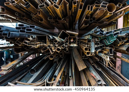 Perspective of pile of construction metals in factory. They consist of square and rectangular steel tubes, iron pipes and bars. - stock photo