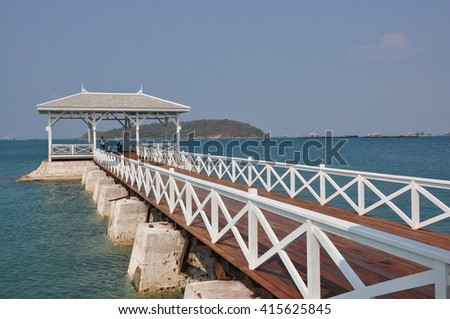 Perspective of white wood bridge to the sea
