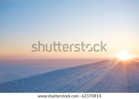 Perspective of winter road on sunset - stock photo