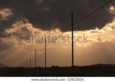 perspective of wooden electricity poles at the sunset against a dramatic and dark sky - stock photo