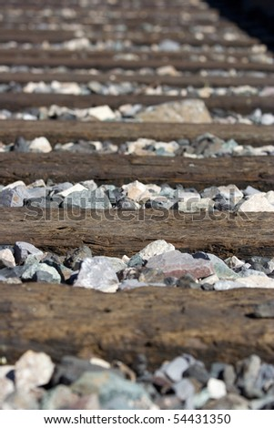 Perspective photo of railroad ties and rocks - stock photo
