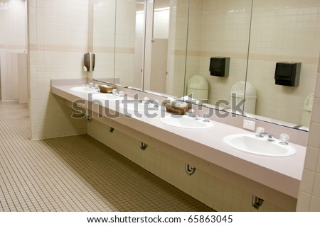 Perspective shot of a countertop with five sinks and mirror