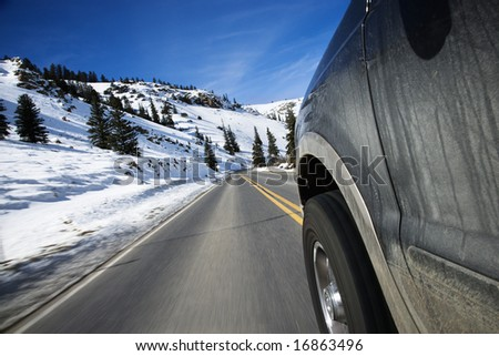 Perspective shot of SUV driving down road in snowy Colorado during winter. - stock photo