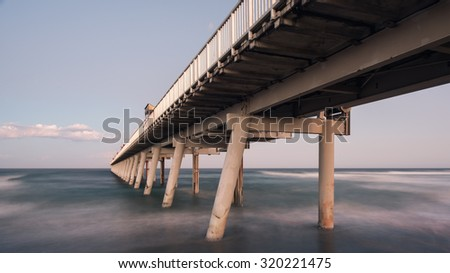 Perspective View Below The Gold Coast Iconic Jetty With a Misty Ocean at Dusk, The Spit, Philip Park, Main Beach, Queensland, Australia - stock photo