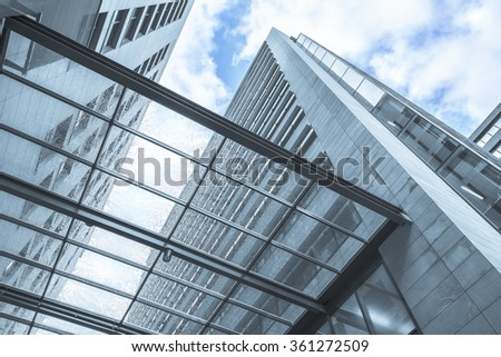 Perspective view from below through transparent wet canopy of modern building - stock photo