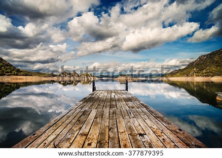 Perspective view of a wooden pier in a completely calm lake with reflections of the sky - stock photo