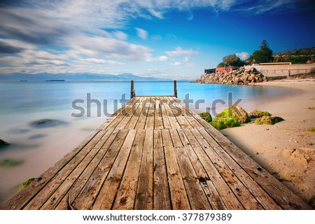Perspective view of a wooden pier on a desert beach with rocks covered with green slime - stock photo