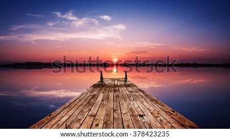 Perspective view of a wooden pier on the pond at sunset with perfectly specular reflection - stock photo