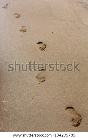 Perspective view of Footprints on the beach - stock photo