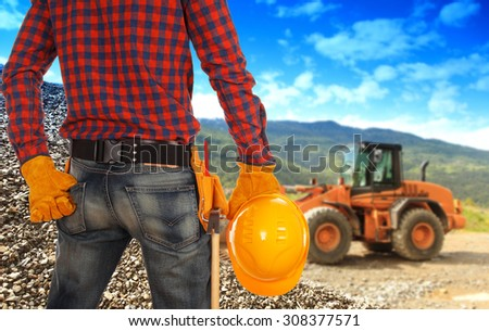 Perspective view of male engineer standing on worksite holding yellow helmet and inspecting construction - stock photo