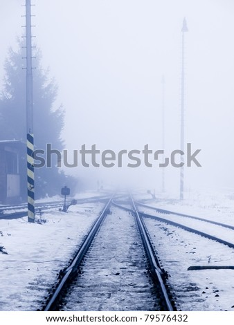 Perspective view of railroad in winter smog - stock photo