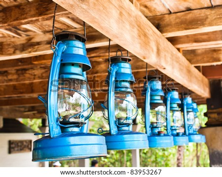 Perspective view of storm lanterns hanged on wooden counterpoise - stock photo