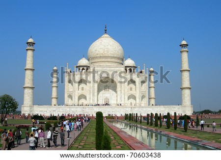 Perspective view of Taj Mahal mausoleum from the main entry gate with reflection in water in Agra, India - stock photo