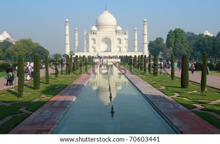 Perspective view of Taj Mahal mausoleum from the main entry gate with reflection in water in Agra, India