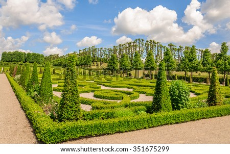 Perspective view of the green flower beds and a gorgeous park under a blue sky with magical clouds near Frederiksborg castle, Hillerod, Denmark - stock photo