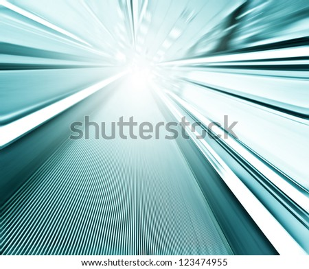 Perspective wide angle view of modern light blue illuminated and spacious high-speed moving commercial escalator with fast blurred trail of handrail in vanishing traffic motion in airport corridor - stock photo