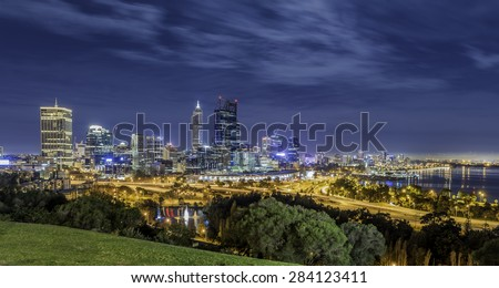Perth, Western Australia, Cityscape at night with cloudy dramatic sky and King Park in the foreground. - stock photo
