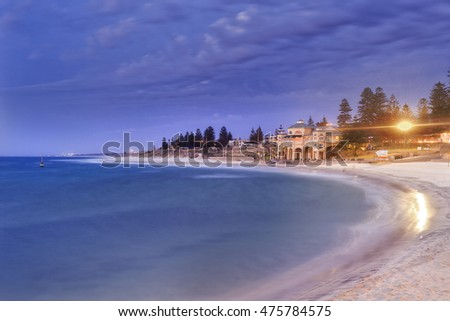Perth western Indian ocean facing sandy beach Cottesloe at sunset. Central pavilion with lights and trees above blurred waves and water.