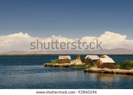 Peru, floating Uros islands on the Titicaca lake, the largest highaltitude lake in the world (3808m). They're built using the buoyant totora reeds that grow abundantly in the shallows of the lake. - stock photo